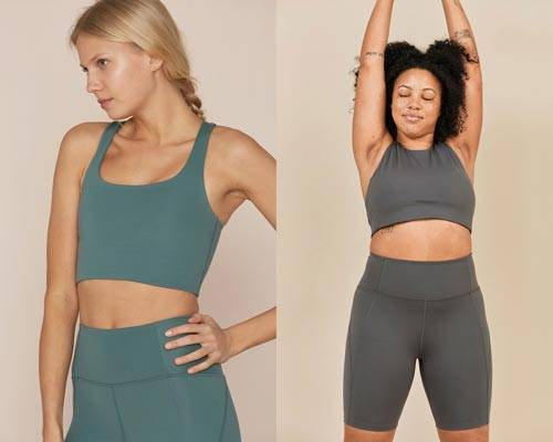 Woman wearing crop sports bra in turquoise with matching high waisted leggings and woman wearing grey crop sports bra and cycling shorts both from sustainable activewear brand Girlfriend Collective