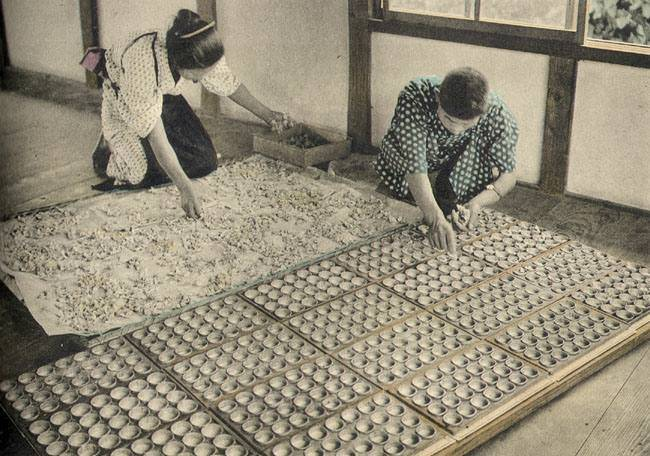 re-coloured image of japanese workers tending to silkworm eggs
