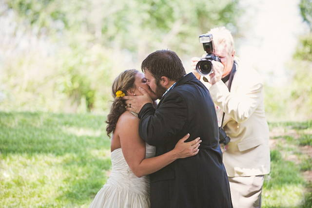 A man shooting from the side of a kissing couple gets in the way of a real photographer and becomes a photobomb