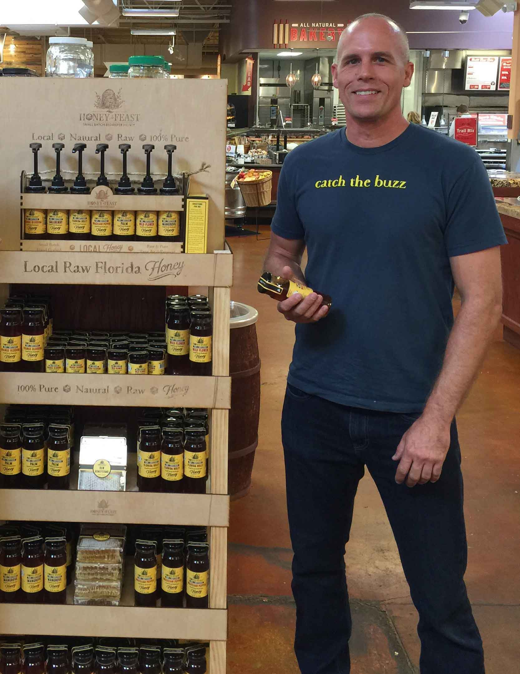 charlie holding a jar of mangrove honey in the store pic