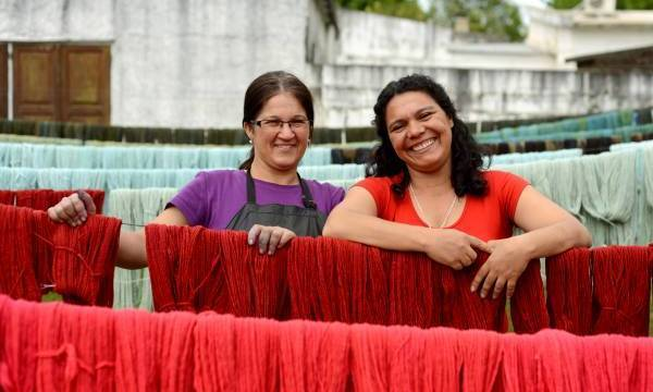 Two women smiling next to rows of died yarn at Manos Del Uruguay
