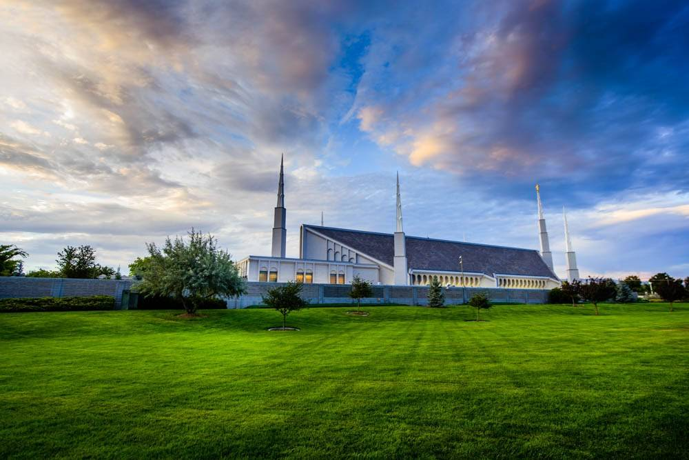 A side-angle photo of the Boise Idaho Temple taken from across a stretch of green grass.