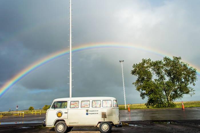 kombi estacionado na beira da estrada com arco-íris no céu nublado