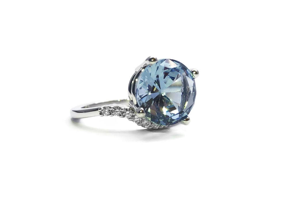 White gold ring on white background with sky blue topaz and diamonds