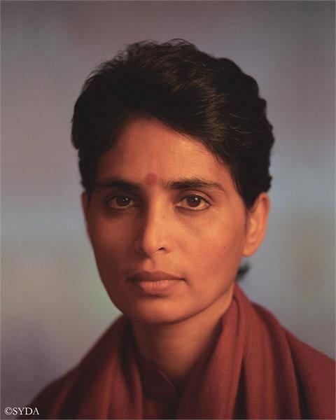 portrait of gurumayi against a grey background