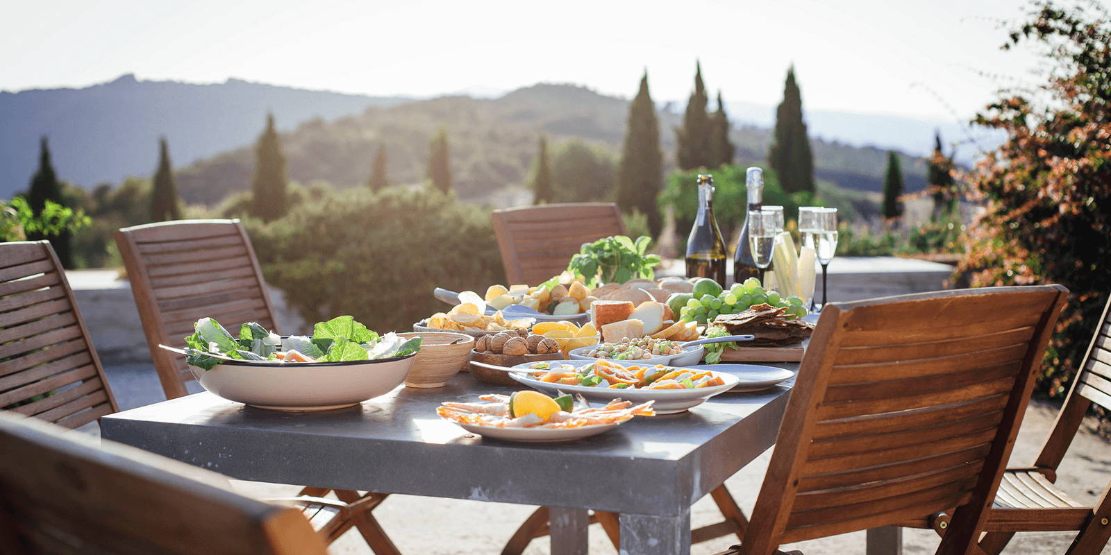 Outdoor table and chairs set with food and wine.