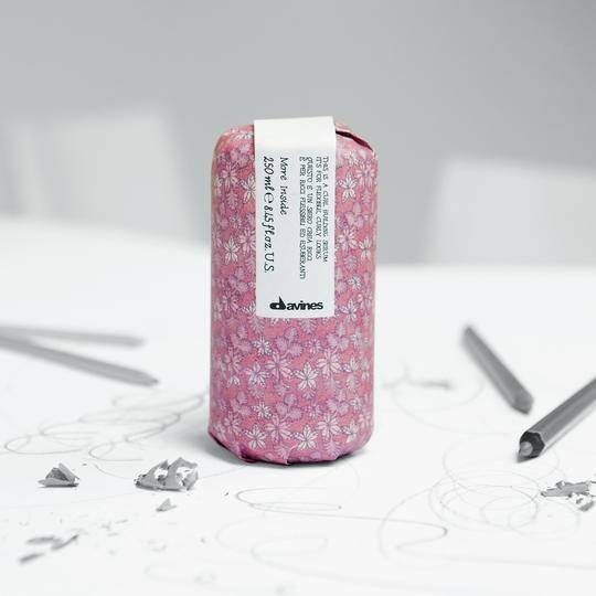A Davines hair product wrapped in pink printed paper