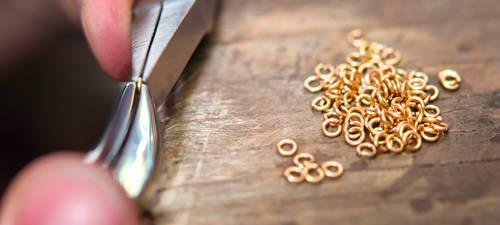 Les mains d'un joaillier fabriquent une chaîne à partir de petits maillons.