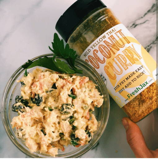 A bowl of coconut curry chicken salad next to a large bottle of FreshJax Organic Mild Yellow Thai Coconut Curry Spice.