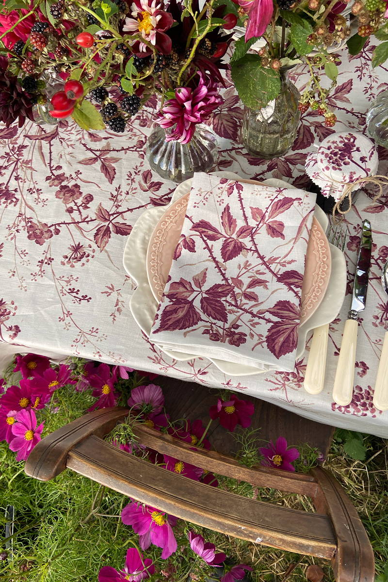 Close up of the Blackberry Print Linen Tablecloth and Napkins tablescape with flowers by Kitten Grayson