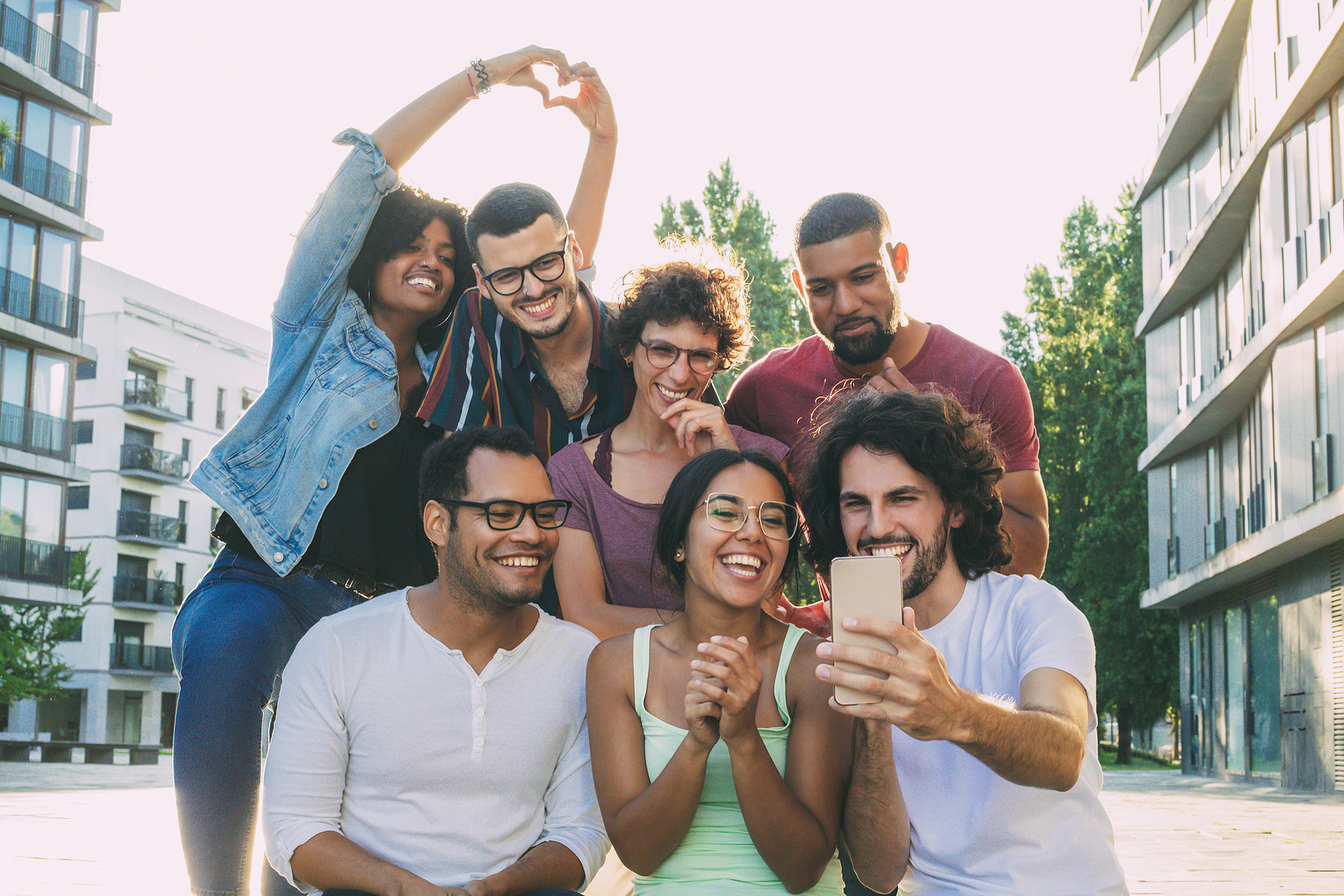 Photo of a group of multi ethnic attractive men and women grouped together trying to take a selfie. Someone made hearts with their hands, they are in a building area.
