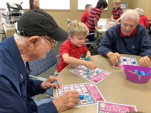 Photo of Kindergarten student doing a craft with assisted living resident