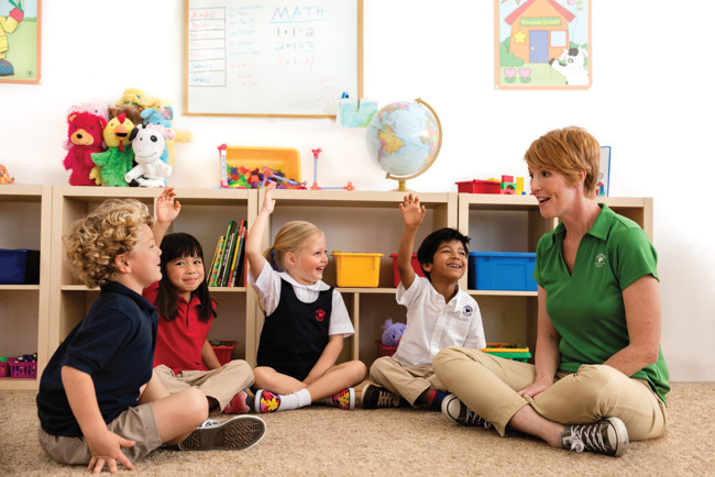 children sitting and raising hands with Primrose School teacher