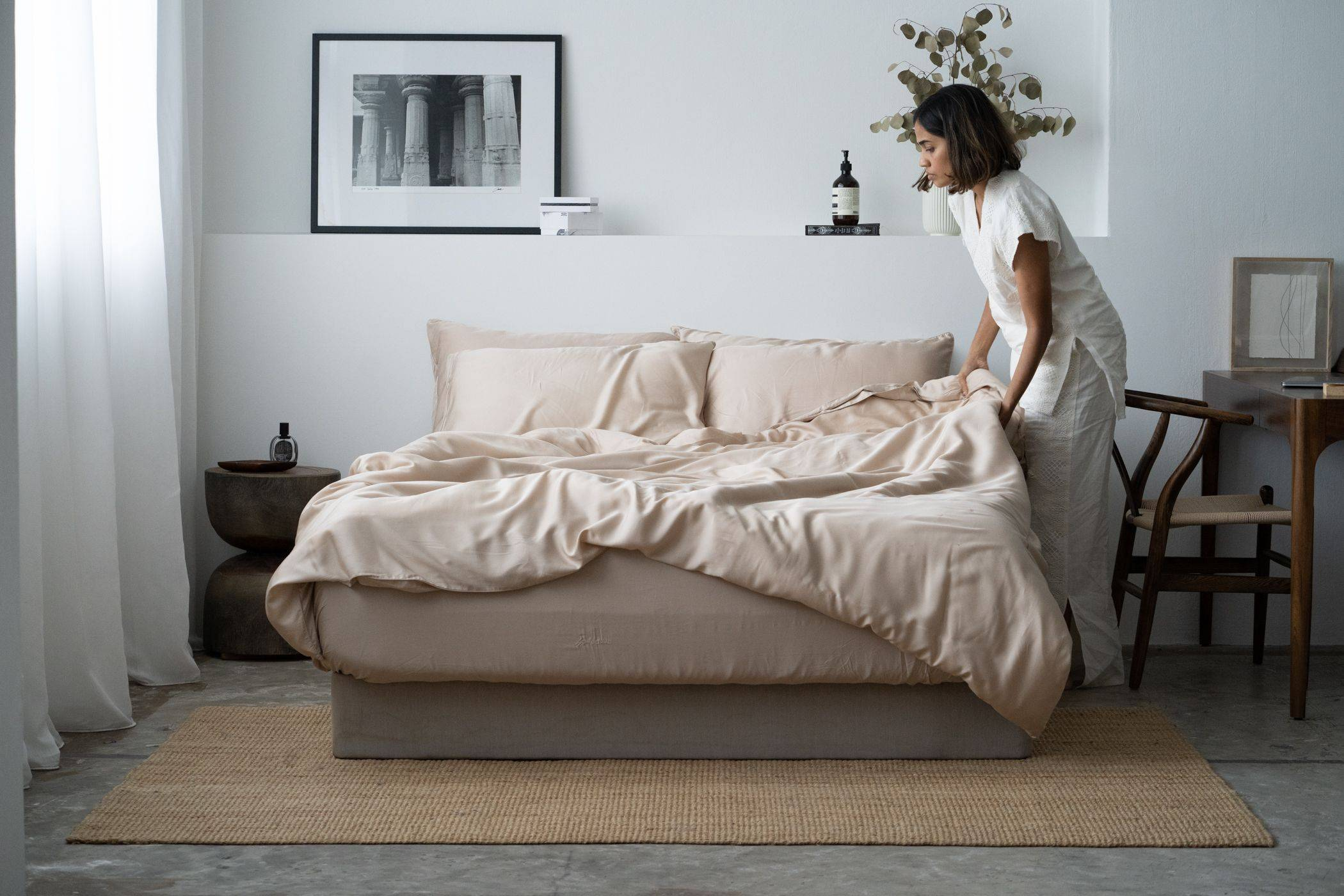 Woman making the bed, featuring Weavve's Lyocell Deluxe Set in Sand Taupe
