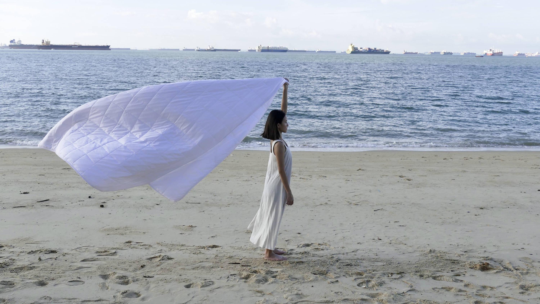 Girl wrapped in Weavve's Lyocell Duvet Insert at the beach