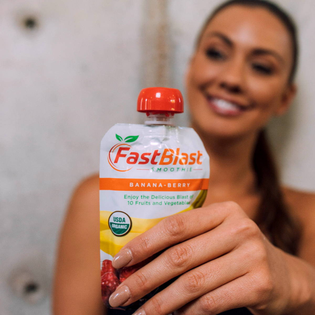 woman holding fastblast banana-berry smoothie pouch