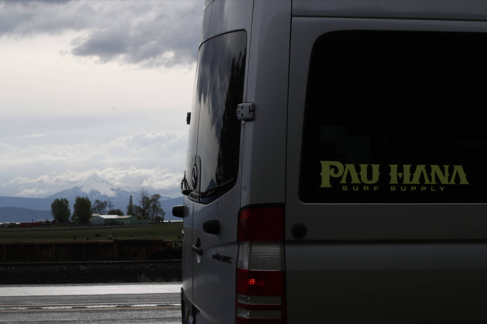 Pau Hana surf supply van with clouds in the background and neon sticker