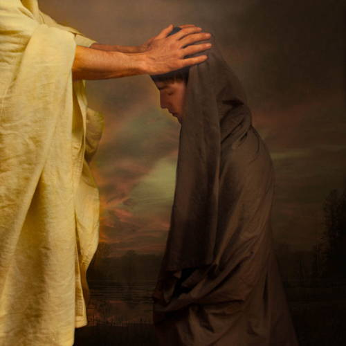 Jesus placing his hands on the head of a younger person, granting a blessing.