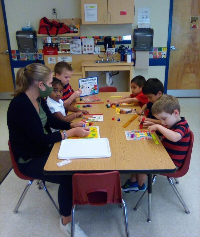 Children wearing uniforms sitting at a table using rulers and cubes to measure different objects