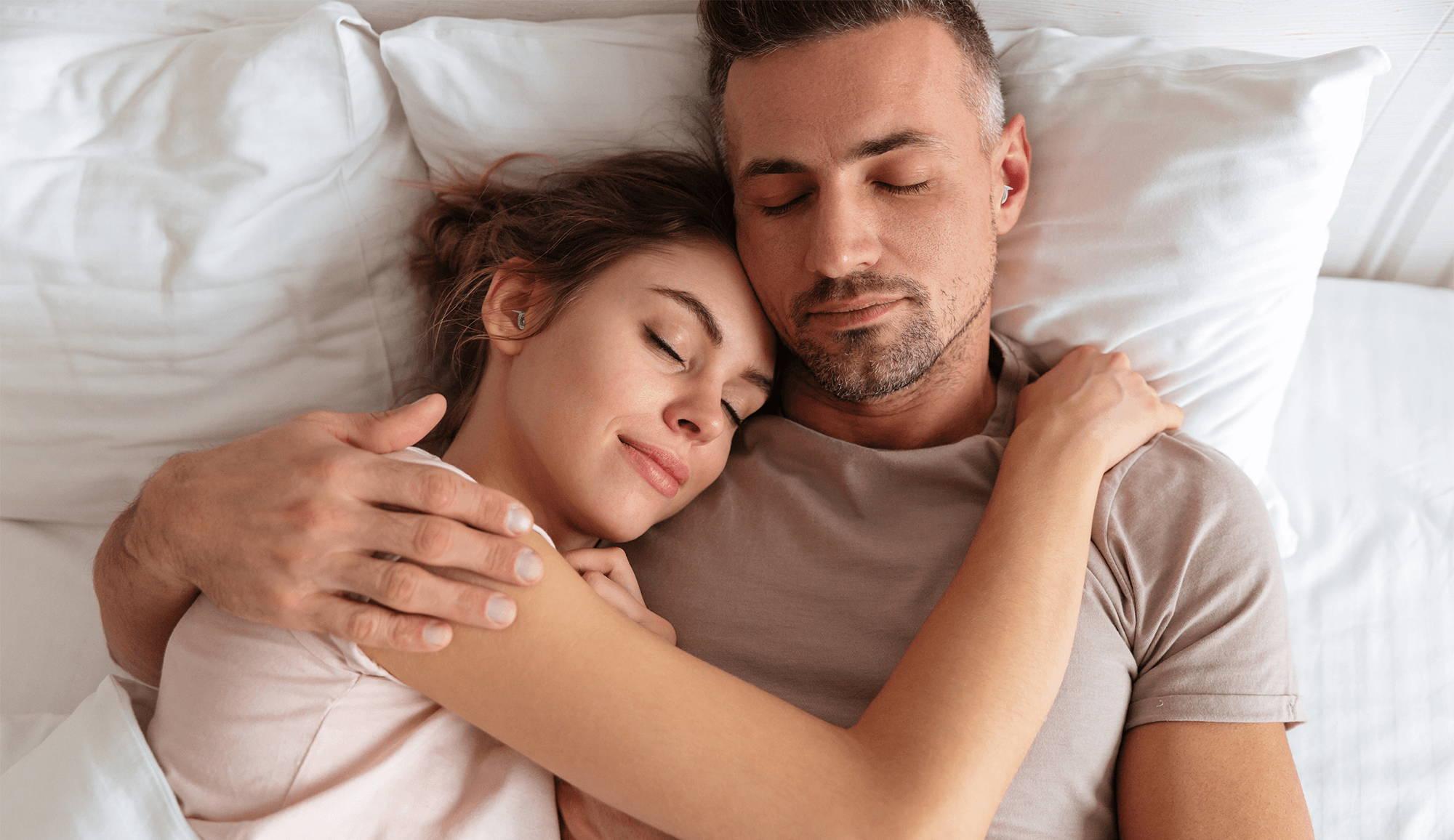 couple sleeps soundly while both wearing earplugs designed for sleeping