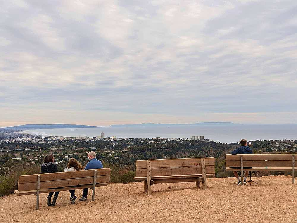 People sitting at benches at Inspiration Point at Will Rogers State Historic Park in Los Angeles