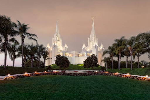 San Diego Temple glowing against a cloudy sky.