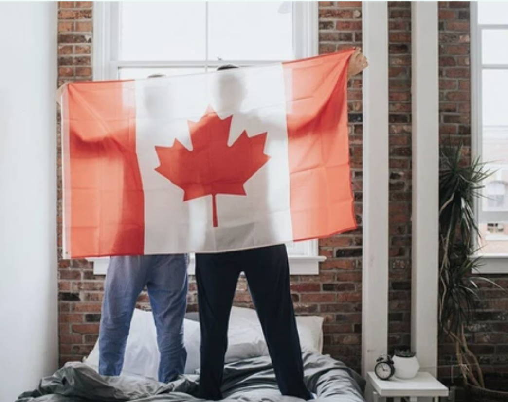 Canadian flag held by two people while standing on a Haven mattress, with bedface sheets.