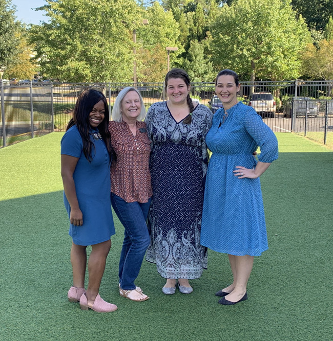 Our management team posed with Mrs. Lockhart on the playground