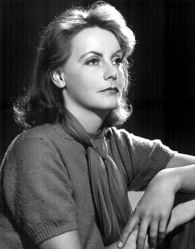 A promotional image for the film, featuring a Greta with a stern look on her face, looking forward with her arms folded on knees.