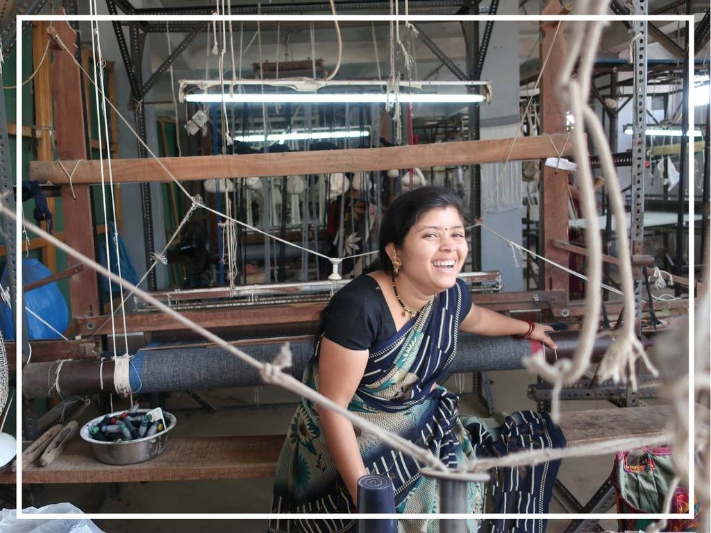 woman on handloom laughing in india