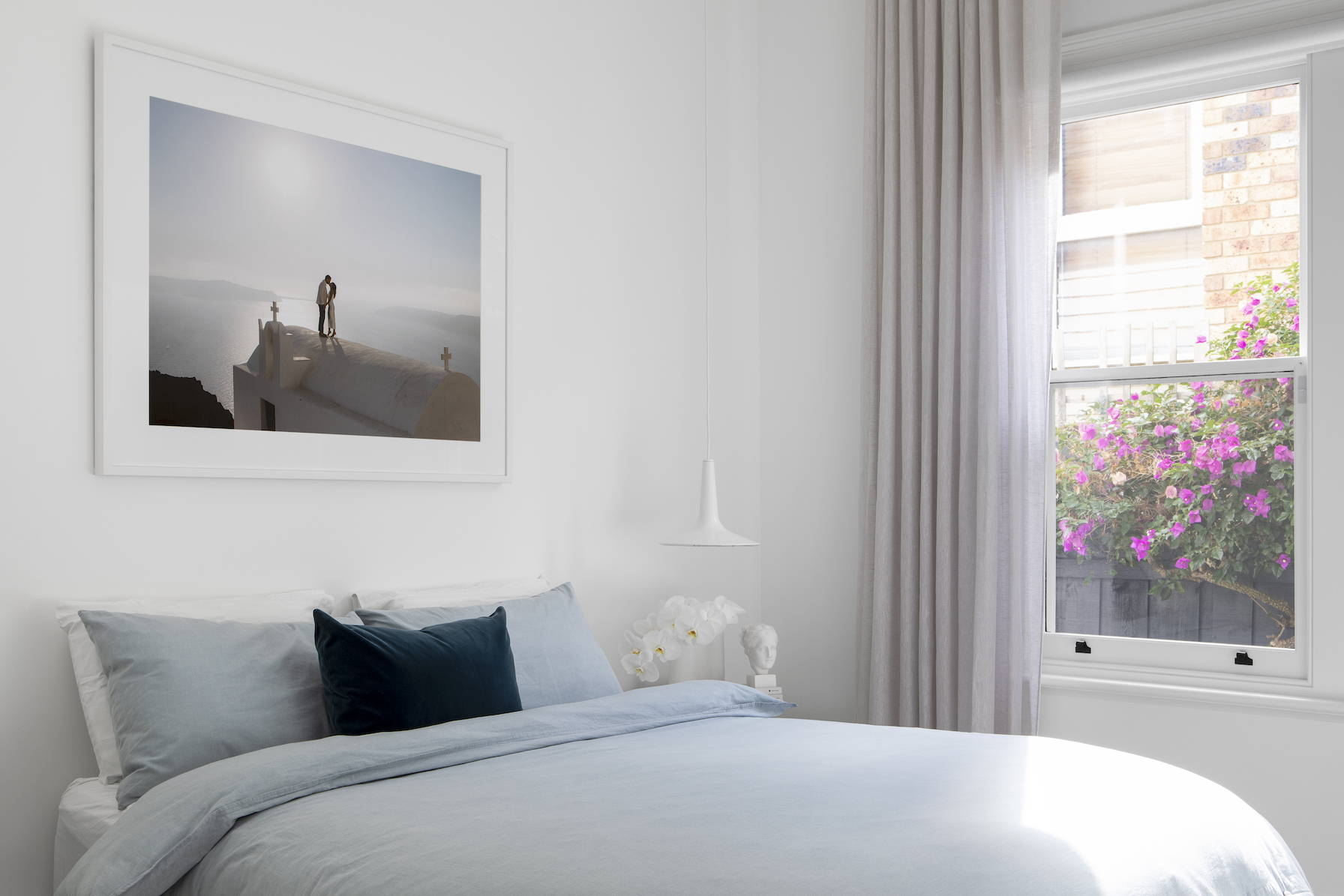 Wedding photography framed and hanging above a bed, the image shows flowering bougainvillea outside the window