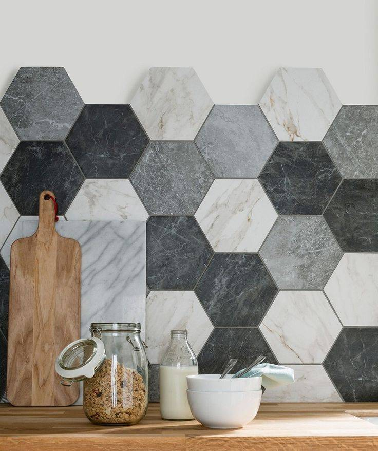 A wooden kitchen counter with a backsplash of hexagonal Exfloorit tiles in greys and white.