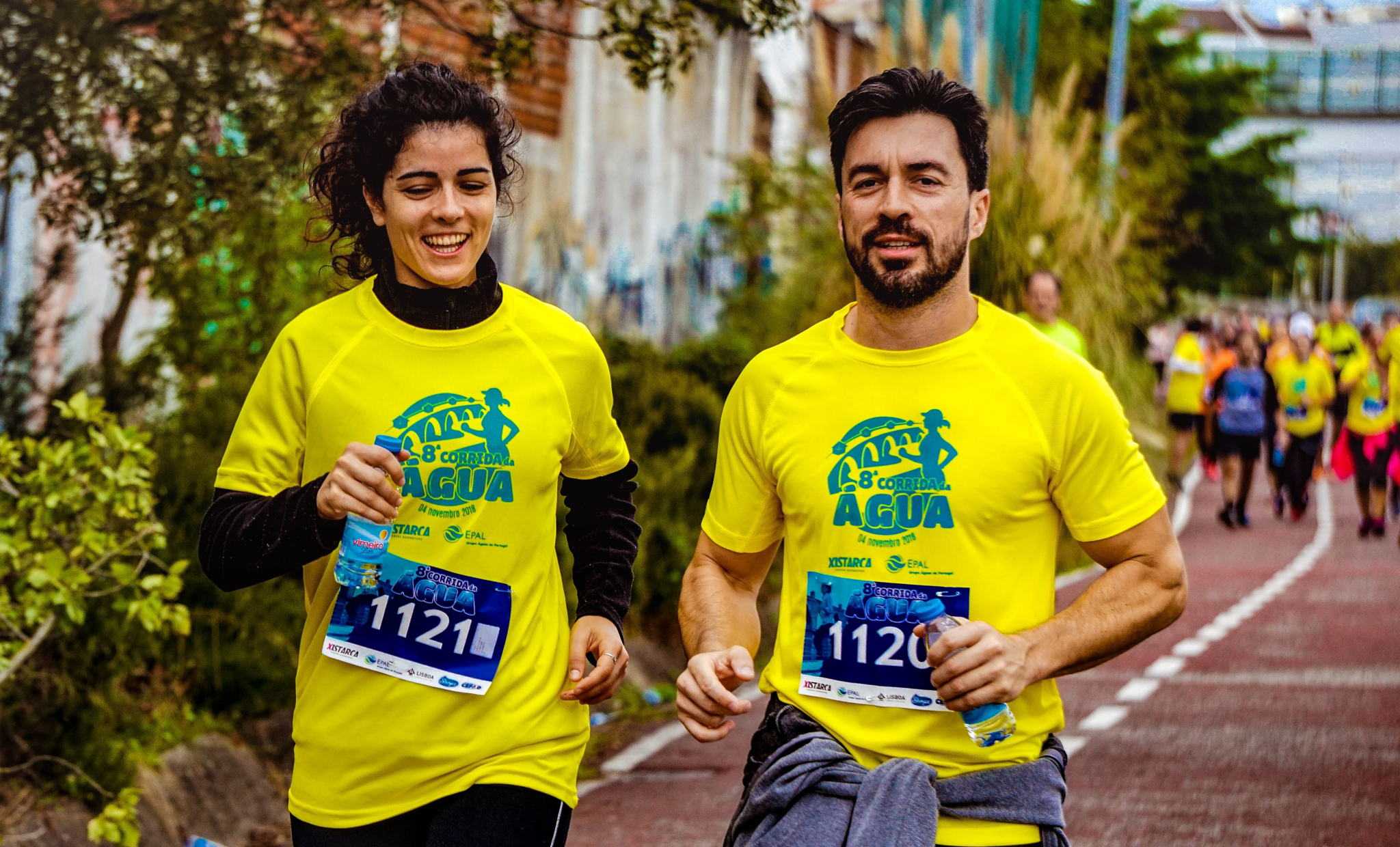 A multi ethnic older man and woman running on a track wearing numbers participating in a race.