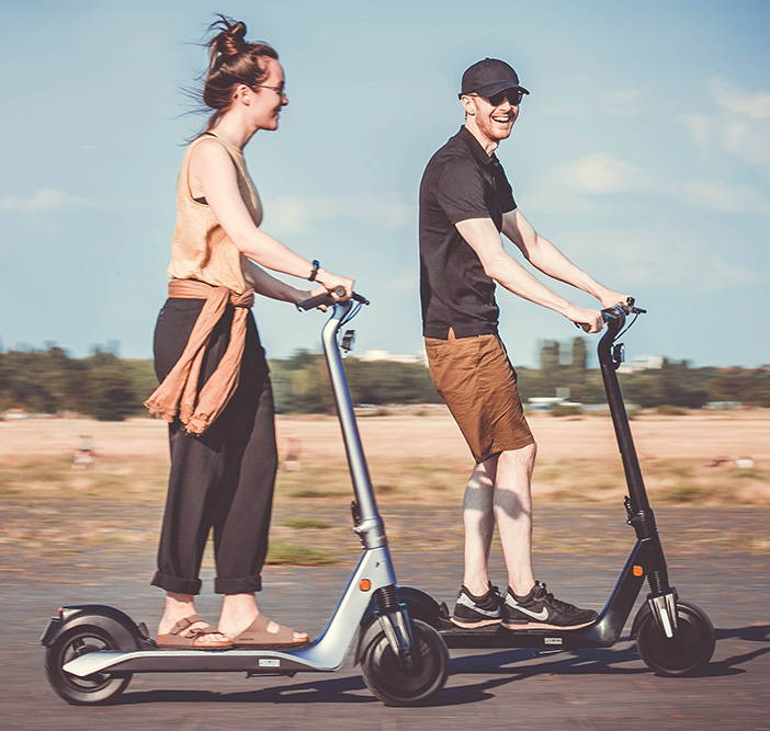 okai-escooter-couple-riding-es500-scooters-smiling-mobile