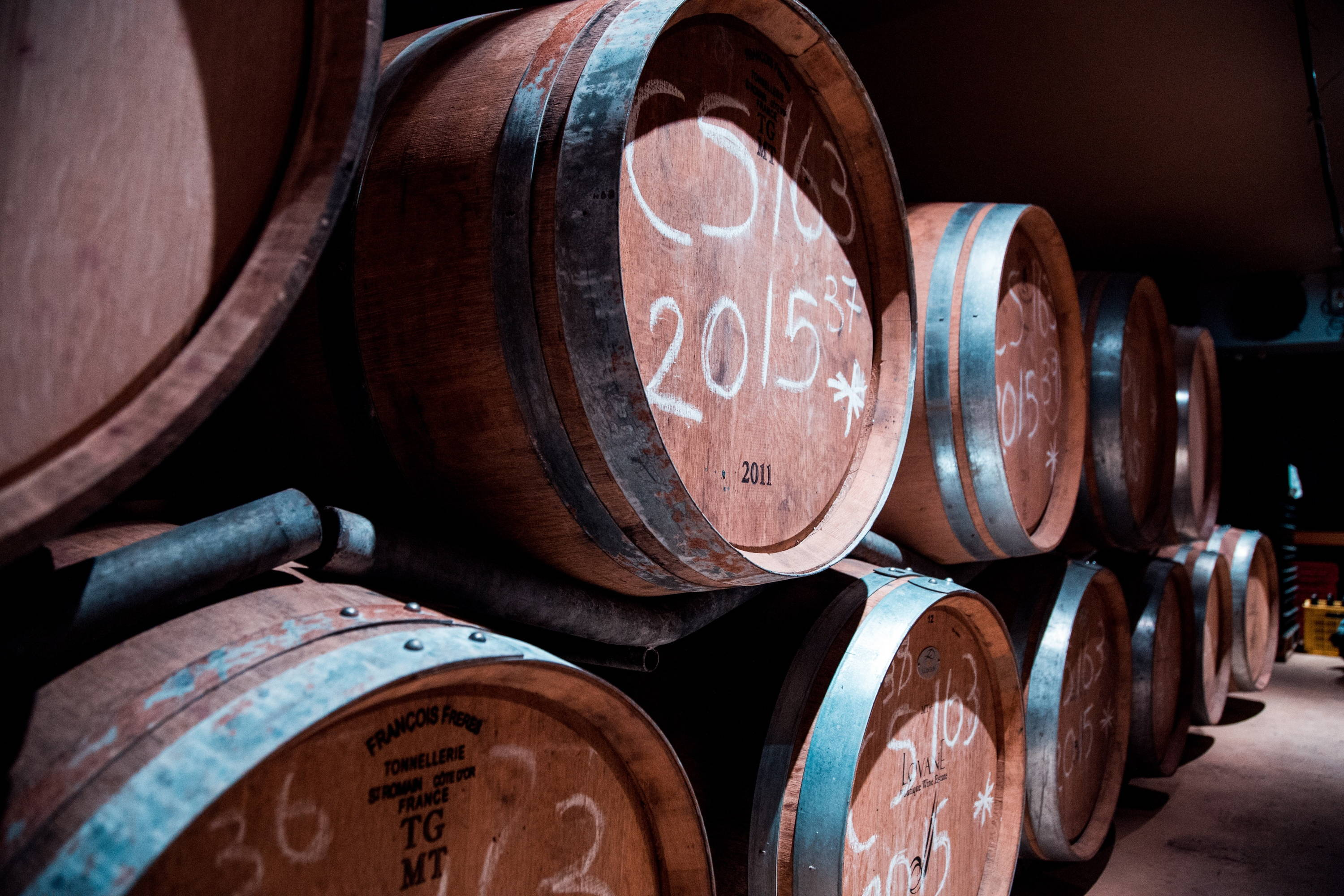 Wine barrels in storage displaying dated wine to compare old world vs new world wine making techniques.