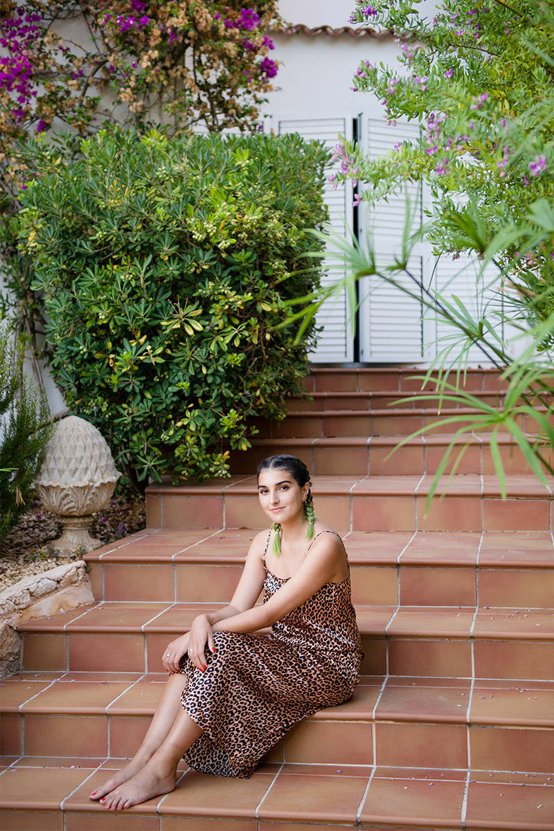 Lauren Mills sits on a stairs to their Ibiza home whilst wearing YOLKE's Classic Leopard Silk Slip