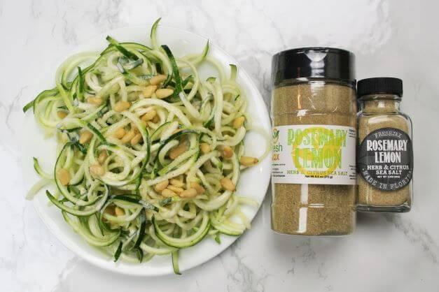zucchini noodles with creamy rosemary lemon sauce next to a large bottle of FreshJax Organic Rosemary Lemon Sea Salt.