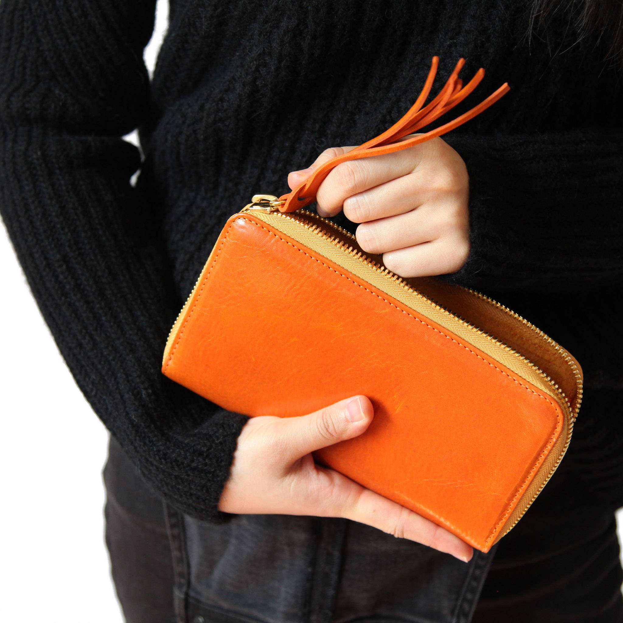 Woman zipping up Stick & Ball Vegetable-tanned Italian leather zip/clutch wallet in orange