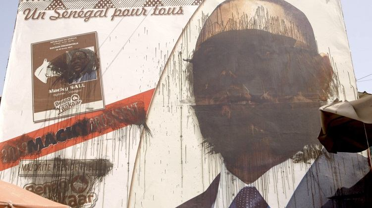 A mural defaced and blacked out by graffiti.