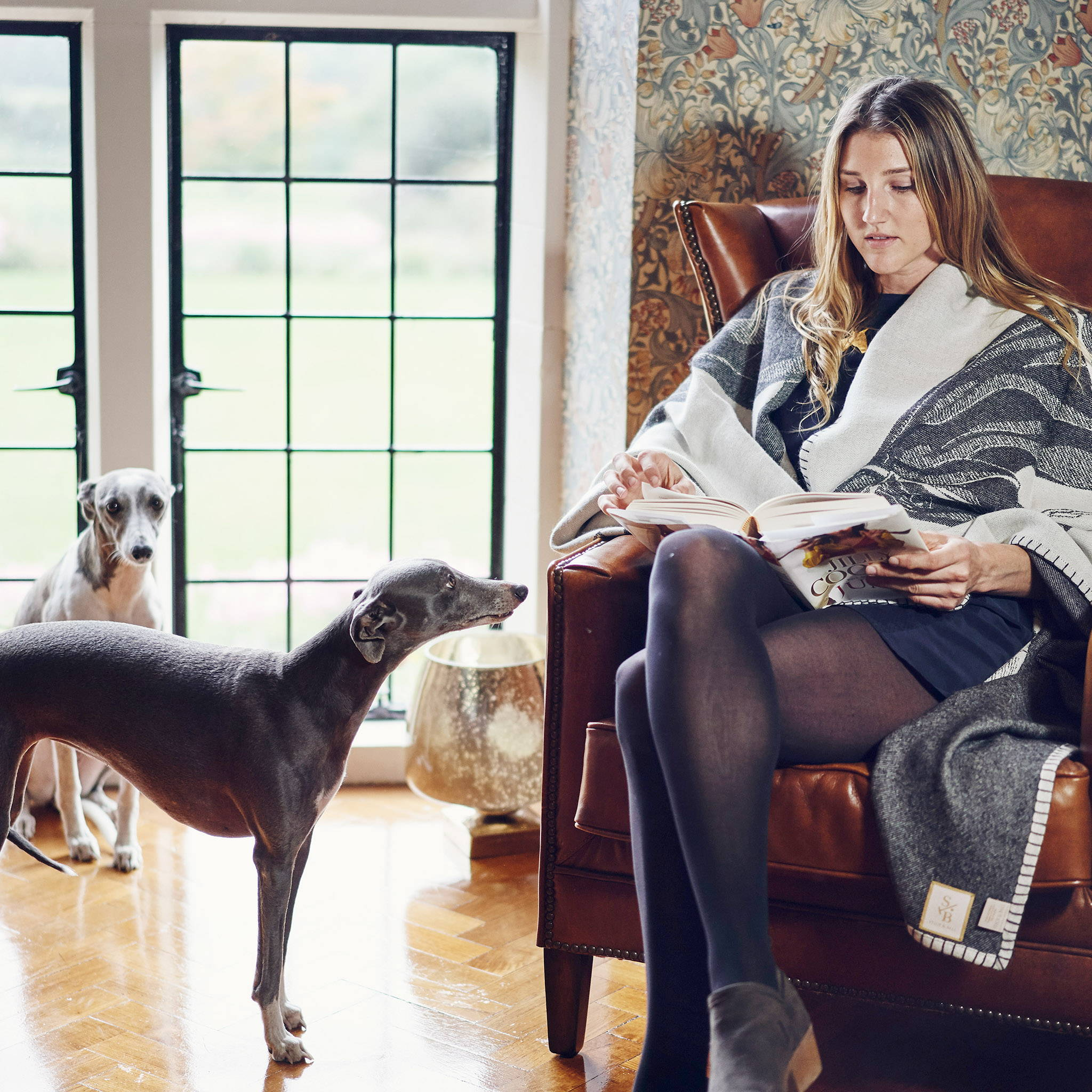 Woman wearing Alpaca Polo Pony Throw Blanket in Charcoal in her home - Stick & Ball