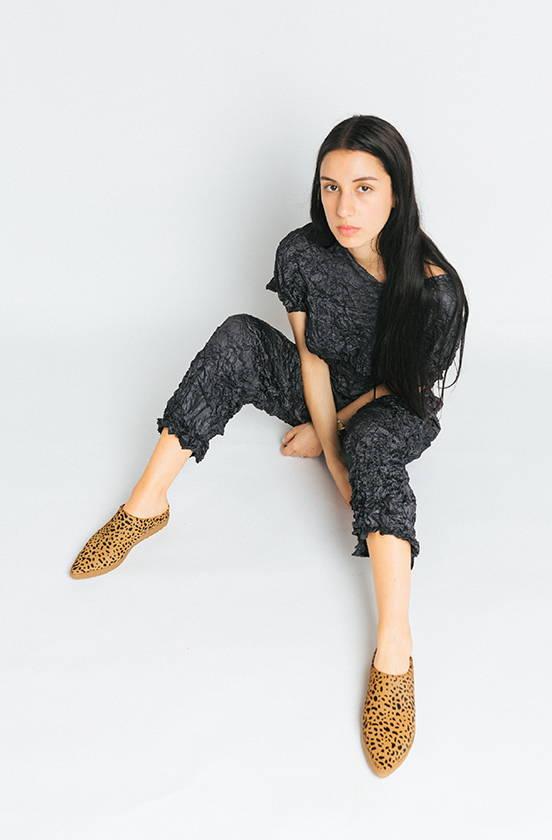 Girl sitting wearing leopard print VQS shoes