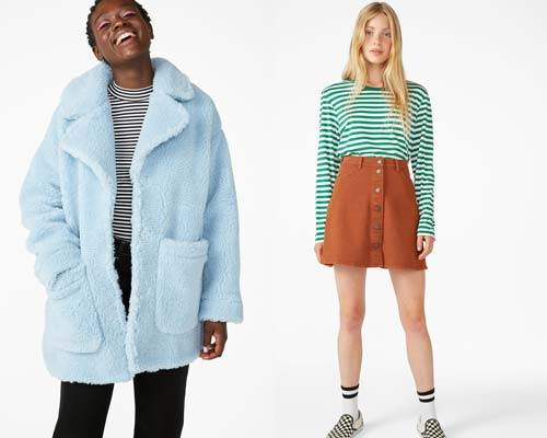 Woman wearing pale blue oversized faux shearling coat made with recycled polyamide with black skinny jeans and striped organic cotton t-shirt and woman wearing green and white striped organic cotton t-shirt with organic cotton ochre orange mini skirt, white tube socks and checkerboard vans, all from sustainable fashion brand Monki