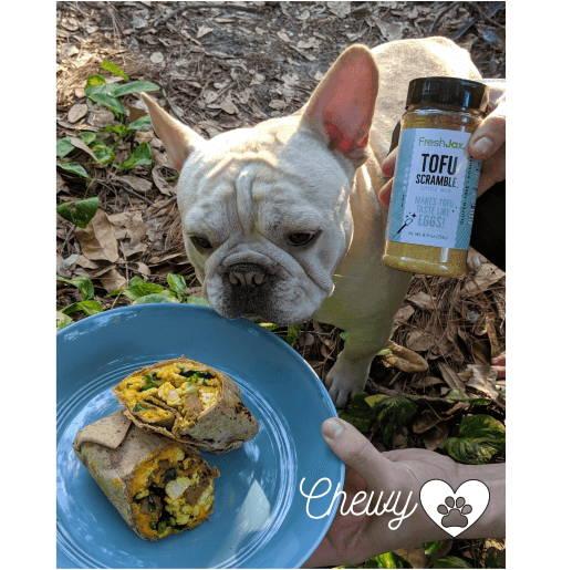 A plate of tofu scramble burritos with a dog and a large bottle of FreshJax Organic Tofu Scramble.