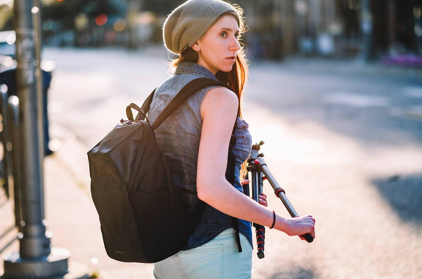 Fotógrafa extendiendo un trípode con una mochila de cámara en la espalda