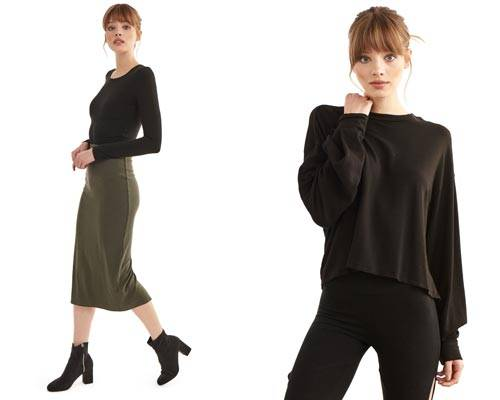 Woman wearing sustainable Groceries Apparel khaki green calf length jersey skirt with a black crew neck long sleeve top and woman wearing black leggings with cropped relaxed fit organic cotton sweatshirt
