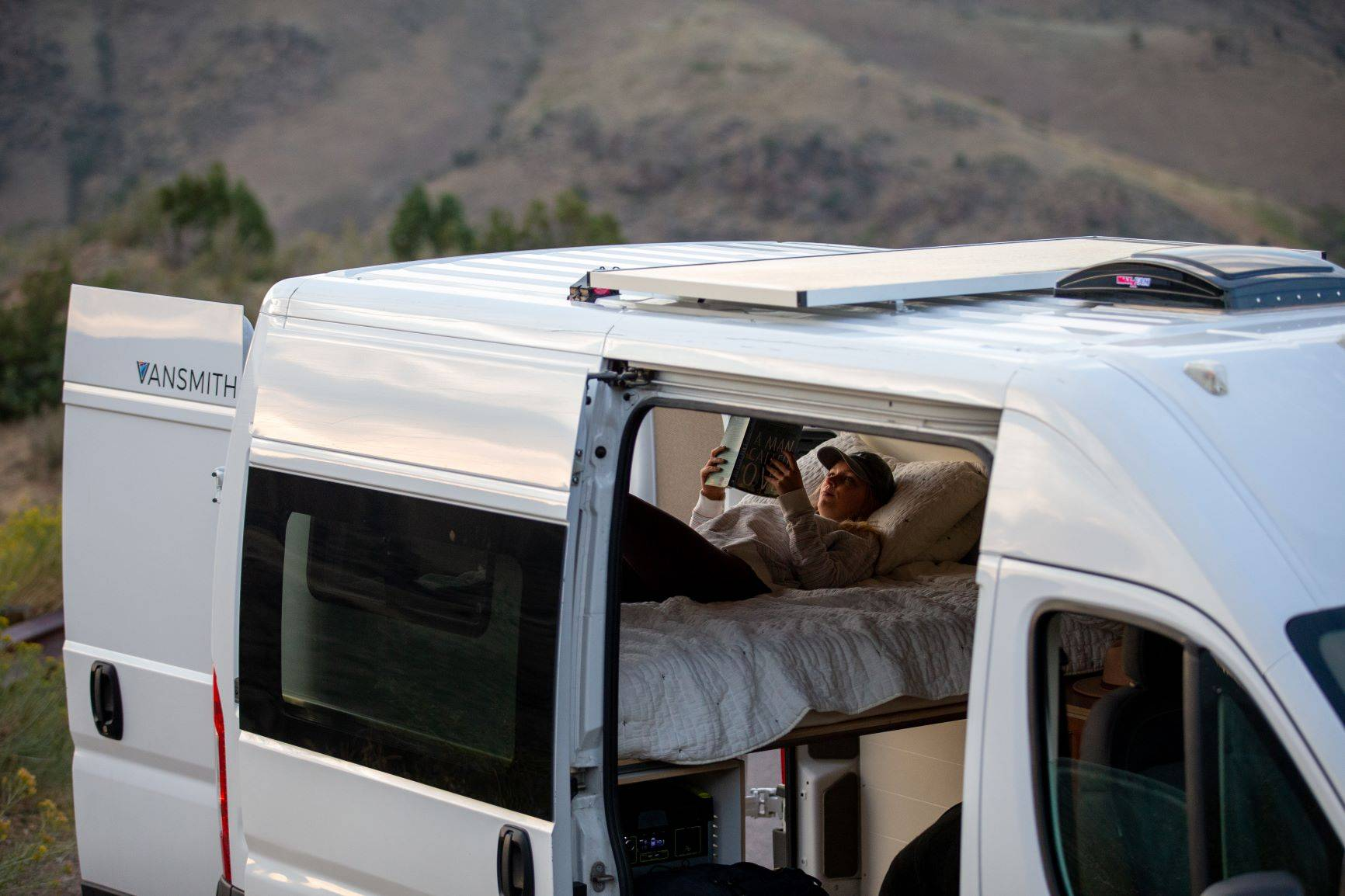 The Bivy - Sprinter 144 / ProMaster 136 Van Conversion - Exterior View of Woman Reading in Bed - The Vansmith