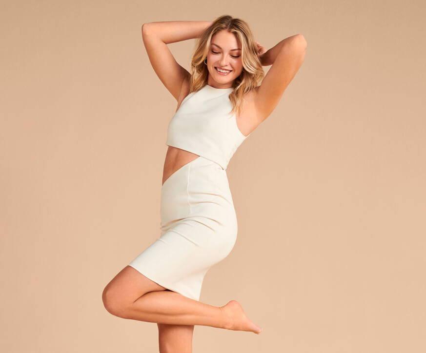 women standing on one leg in white dress