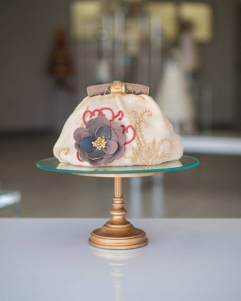 Special Occassion Cake shaped like a purse with a flower on the side. Made exclusively at House of Clarendon in Lancaster, PA