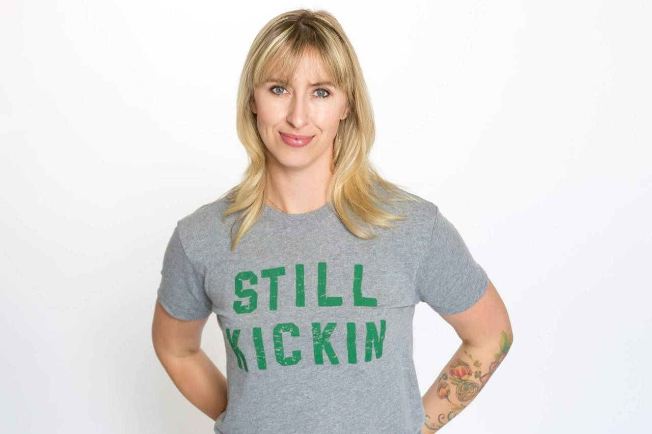 photo of Nora McInerny wearing a grey t-shirt with green Still Kickin print