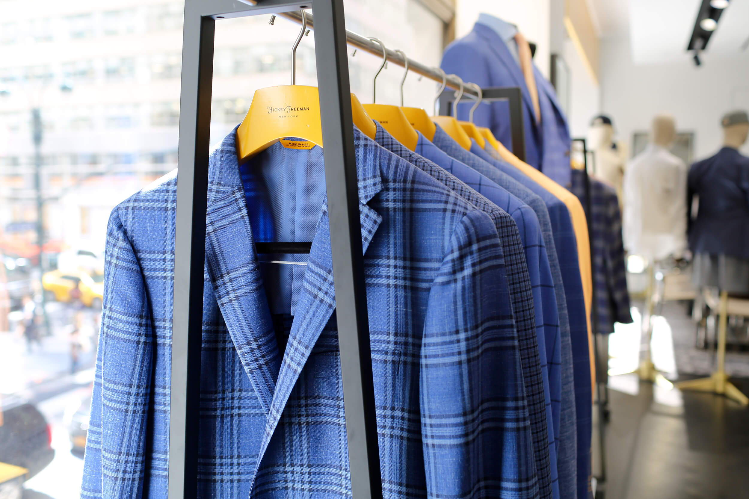 Blue Hickey Freeman Jackets hanging on a rack from inside of the store